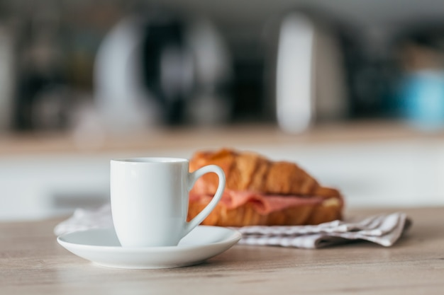 Breakfast of coffee and croissant sandwich stuffed with salami at the kitchen