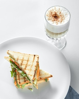 Концепция завтрака - чашка кофе с тостами на белой поверхности