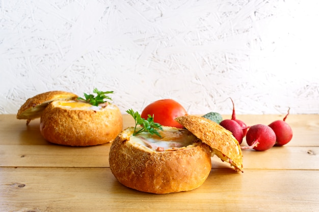 Breakfast concept for two. baked eggs in a bun with fresh vegetables.