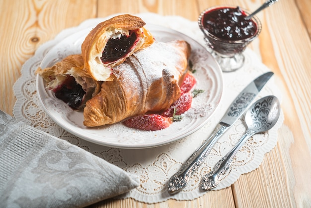 Breakfast concept with coffee cup, croissants, cream and fresh berries
