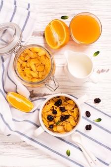 Breakfast concept with corn flakes, milk and orange juice
