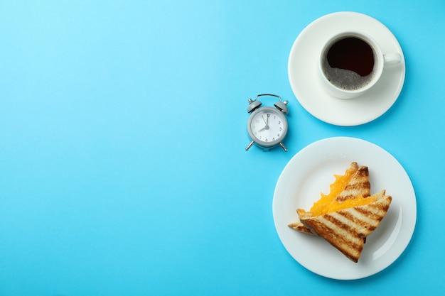 파란색 배경에 구운 샌드위치와 아침 식사 개념