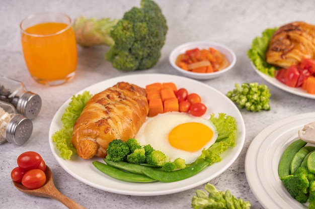 Breakfast consisting of bread, fried eggs, broccoli, carrots, tomatoes and lettuce on a white plate.