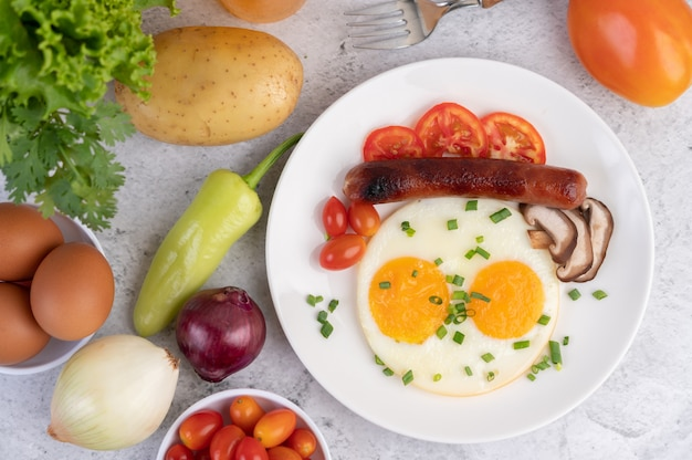 Breakfast consisting of bread, fried eggs, tomatoes, chinese sausage and mushrooms.