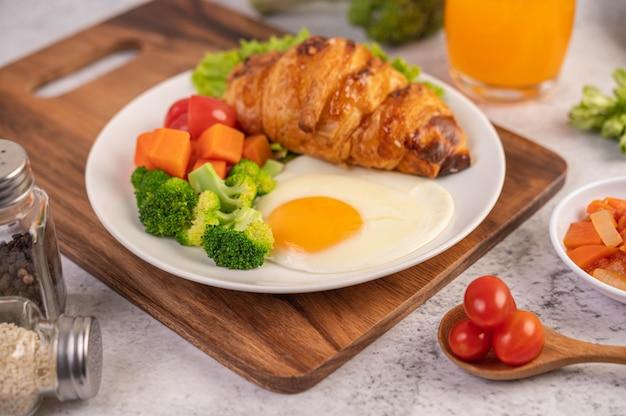 朝食は、パン、目玉焼き、ブロッコリー、ニンジン、トマト、レタスの白い皿の上で構成されます。