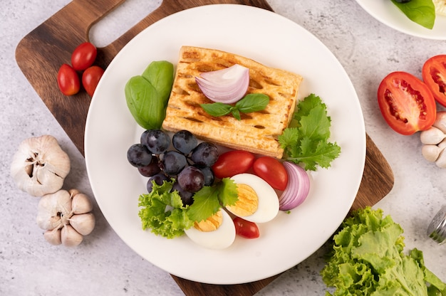 Breakfast consists of bread, boiled eggs, black grape salad dressing, tomatoes, and sliced ​​onions.