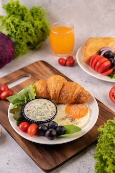 Breakfast consists of croissant, fried egg, salad dressing, black grapes, and tomatoes.