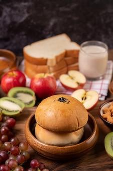 朝食は、木製のテーブルにパン、リンゴ、ブドウ、キウイで構成されています