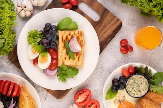 Завтрак состоит из хлеба, вареных яиц, салата из черного винограда, помидоров и нарезанного лука.
