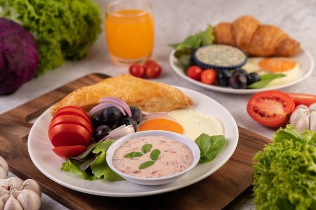 朝食は、パン、目玉焼き、サラダドレッシング、黒ブドウ、トマト、スライスした玉ねぎで構成されています。