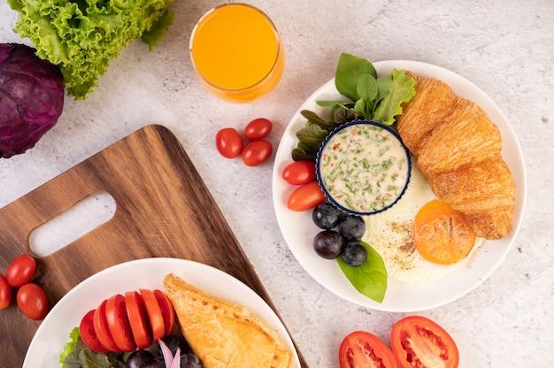 Завтрак состоит из круассана, жареного яйца, заправки для салата, черного винограда и помидоров.