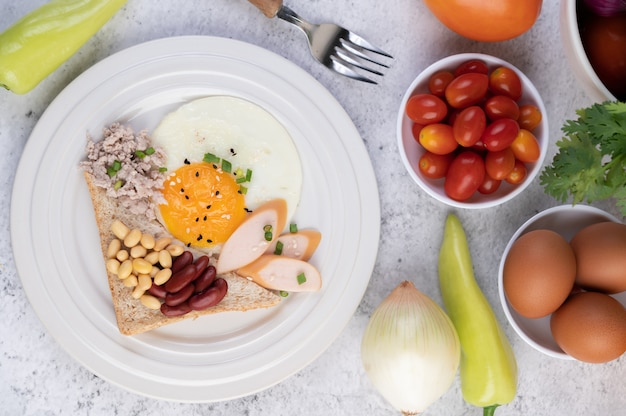 朝食は目玉焼き、ソーセージ、豚ひき肉、パン、小豆、大豆の白い皿で構成されています。