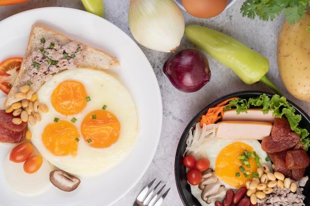Завтрак состоит из яичницы, колбасы, рубленой свинины, хлеба, красной фасоли и сои на белой тарелке.
