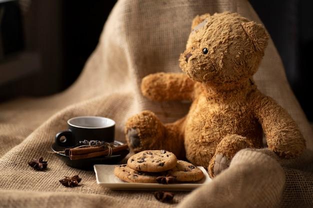 Завтрак, печенье и кофе с корицей и плюшевым мишкой.