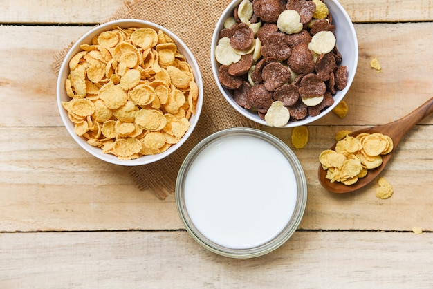 Breakfast cornflakes and various cereals in bowl and milk cup