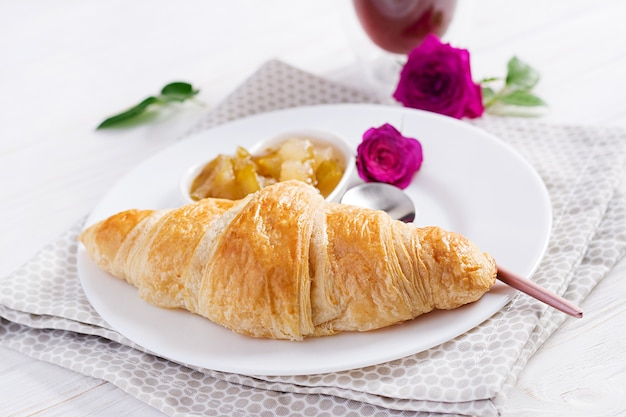 Breakfast - croissant, jam and coffee.