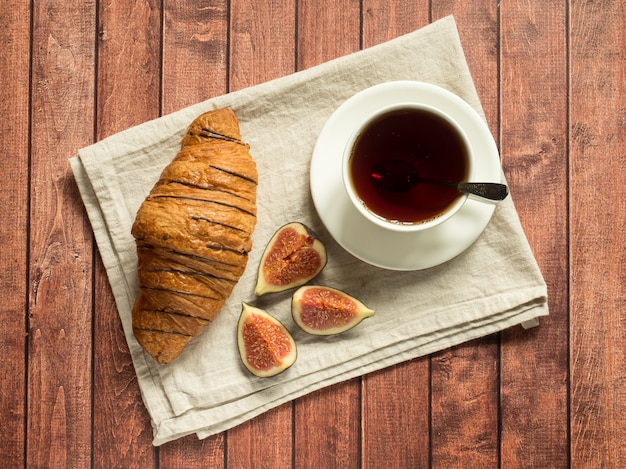 Breakfast croissant and tea on a textile napkin, dark wooden surface