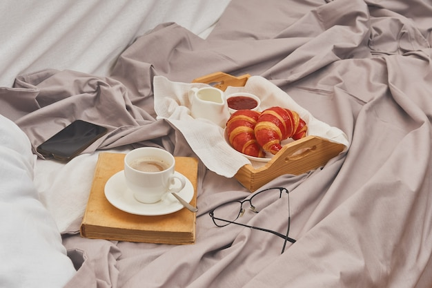 Breakfast on a crumpled bed, coffee, croissants, book, mobile phone