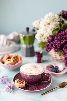 Breakfast cup of coffee, waffles, milk and cream and lilac flowers. morning