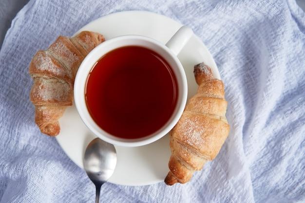 Чашка чая для завтрака и свежие домашние круассаны на белой салфетке, вид сверху