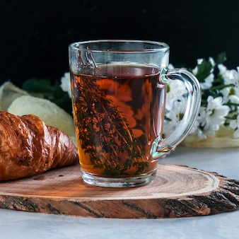 Breakfast cup of tea with thyme and croissant