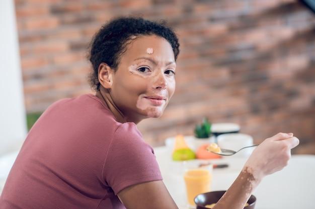 아침밥. 집에서 아침 식사를 하는 검은 피부의 젊은 여성