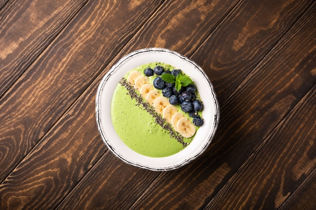 Breakfast detox green smoothie bowl from banana and spinach on wooden surface