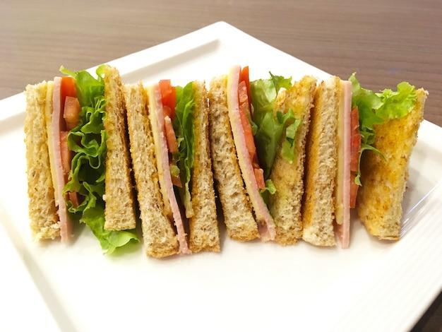 朝食ダイエット食品。朝、木製のテーブルの上に白いプレートにレタス、ハム、黄色いチーズをサンドイッチした全粒粉パン。
