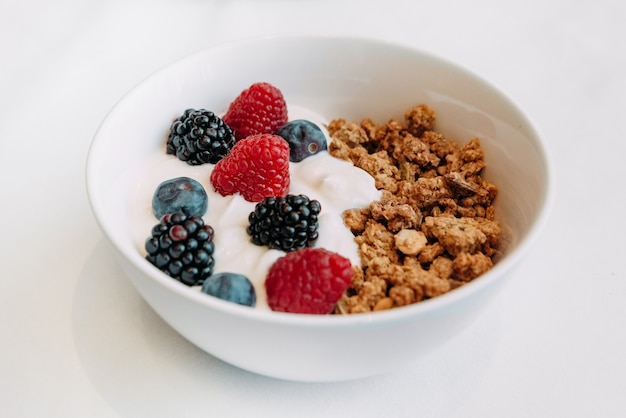 Breakfast dish granola with yogurt and fresh fruit raspberries blueberries in a plate top view isolated