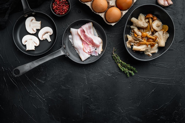 Смесь ингредиентов яиц для завтрака в чугунной сковороде, на черном фоне, плоская планировка, вид сверху, с пространством для текста copyspace