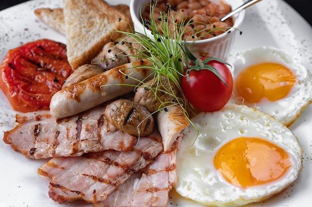 朝ごはん。卵、ベーコン、キノコ、トースト、豆、白い皿の上