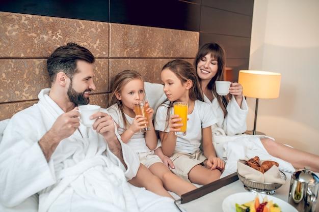 Завтрак. семья в белых халатах, лежа в постели и завтракающая