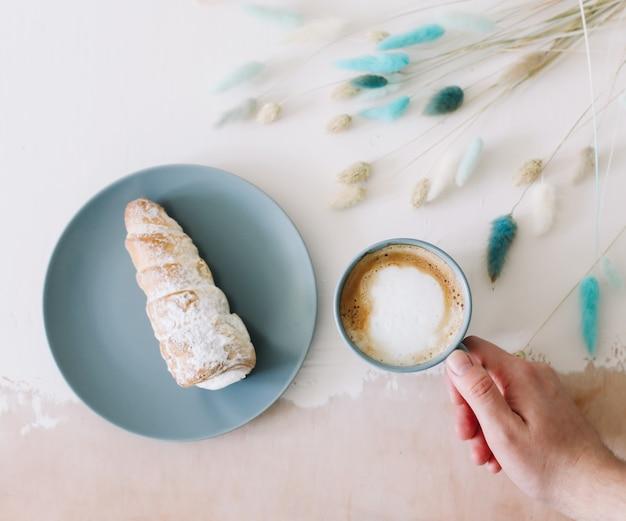 Плоская кладка для завтрака с вкусными сливочными слоеными булочками на тарелке и чашкой капучино, вид сверху
