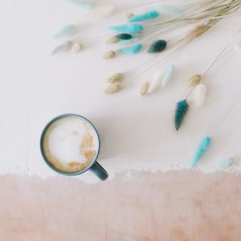 Плоский стол для завтрака с большой кружкой молочного кофе капучино и цветами