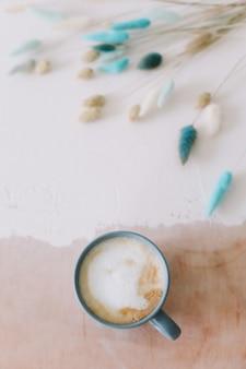 Плоский стол для завтрака с большой кружкой молочного кофе капучино и цветами Premium Фотографии