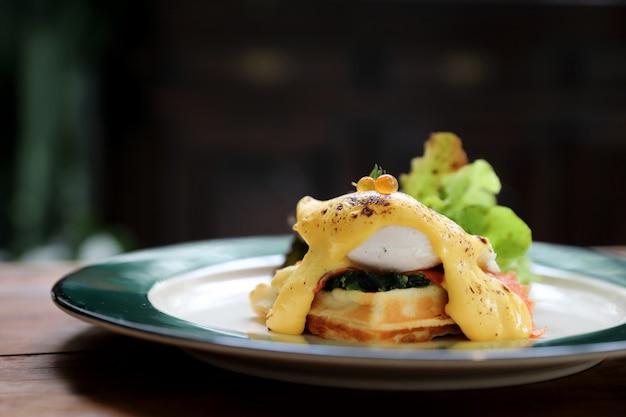 Еда на завтрак в виде яичного бенедикта с вафлями и копченым лососем