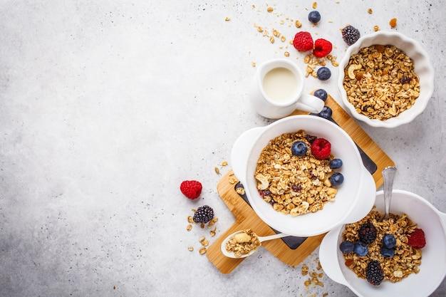 朝食の食べ物の背景。白いテーブル、上面図、コピースペースに牛乳とベリーとグラノーラ。