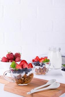 Еда на завтрак. йогурт с ягодами, фруктами и мюсли в стеклянных чашках. copyspace