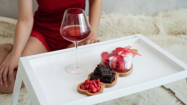 여자친구를 위한 아침식사. 발렌타인 데이 아침. 흰색 쟁반에 있는 와인과 과자. 침대에서 아침 식사. 배경에 빨간 peignoir 소녀