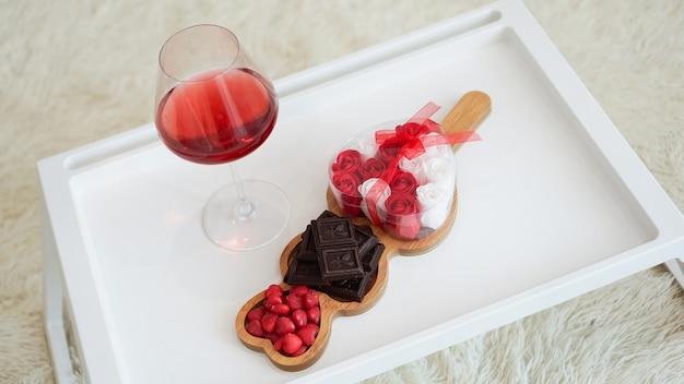 Завтрак для подруги. утро дня святого валентина. вино и сладости на белом подносе. завтрак в постель.
