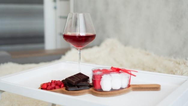여자친구를 위한 아침식사. 발렌타인 데이 아침. 흰색 쟁반에 있는 와인과 과자. 침대에서 아침 식사.