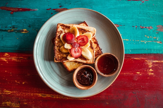 Breakfast french toast sliced fruits banana strawberry and cups of syrup on wooden color table