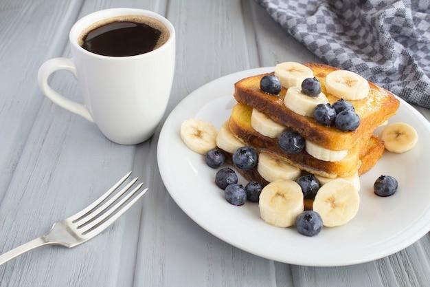 朝食:灰色の木製の背景にブルーベリー、バナナ、蜂蜜、コーヒーとフレンチトースト。閉じる。