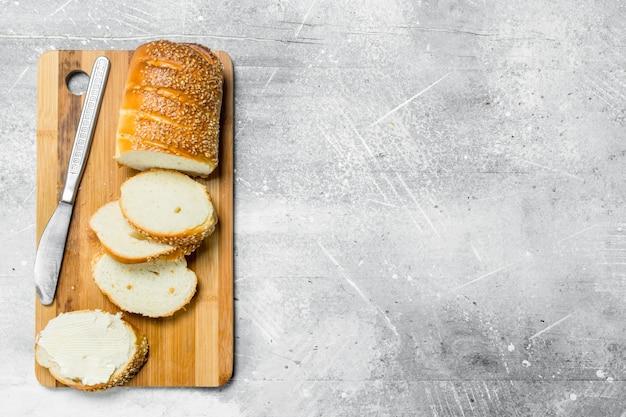 아침밥. 나무 보드에 신선한 빵과 버터. 소박한 테이블에.