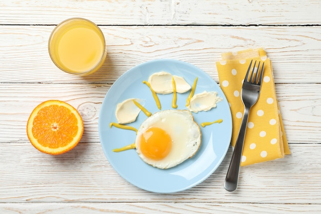 Breakfast of fried egg and orange juice on wooden table, top view