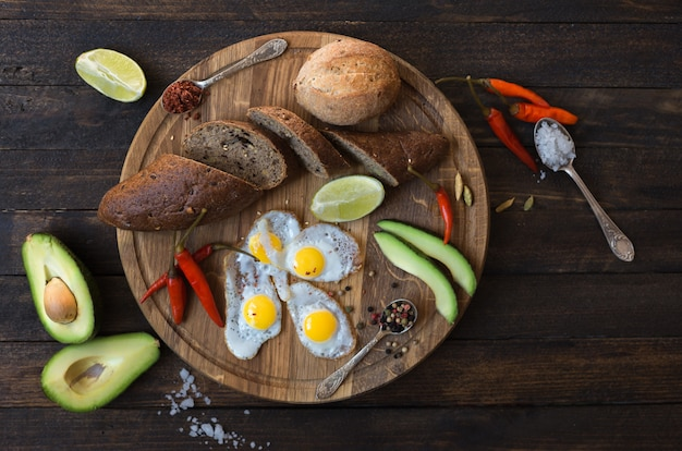 Breakfast of fried eggs, bread, avocado and various spices on a wooden board.
