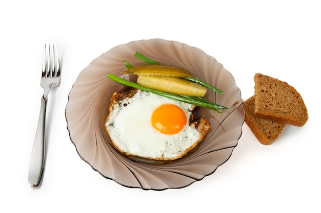 Breakfast fried eggs on a glass plate, with a marinaded cucumber, fresh onions and rye bread