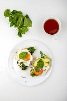 Breakfast . fried eggs on a toasts bread with avocado, spinach and seeds on a white plate with cup of tea. top view.