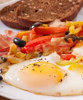 Завтрак - яичница с беконом, помидорами, оливками и кусочками сыра