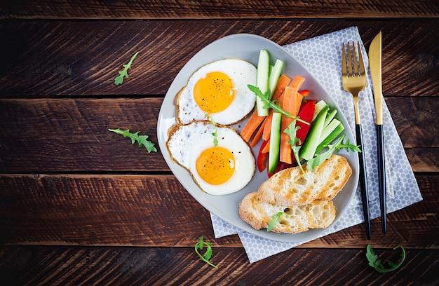 Завтрак. жареные яйца со свежей морковью, огурцом, паприкой и тостами на деревянных фоне. вегетарианская еда. вид сверху, копировать пространство